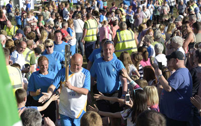 The baton bearer makes his way through the crowds in Dalkeith