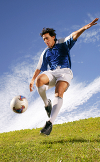 Footballer in a blue top kicking a ball