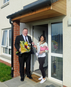 Councillor presenting flowers to tenant at front door of house