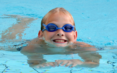 Young person with goggles on swimming
